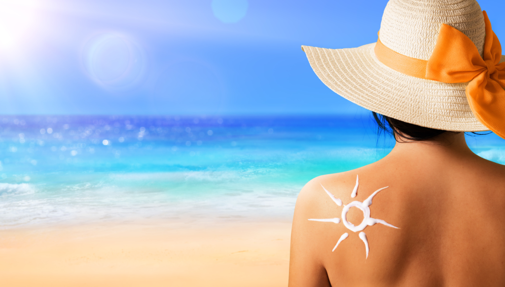 Fotoprotezione - donna in spiaggia, con cappello e crema solare
