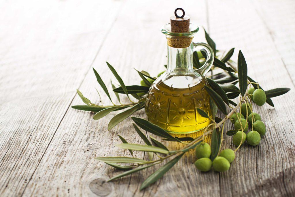 Olio extravergine di oliva - bottiglietta con olio extraverginde d'oliva, circondata da un ramoscello coi frutti
