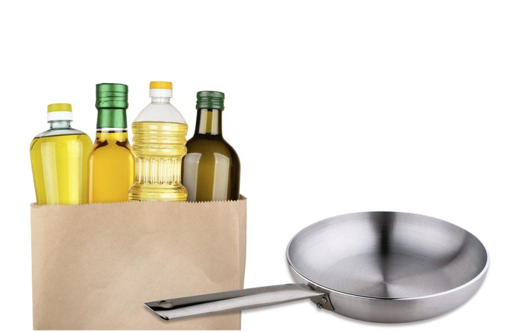 Oli per friggere . bottiglie d'olio dentro un sacchetto, vicino a una padella.
