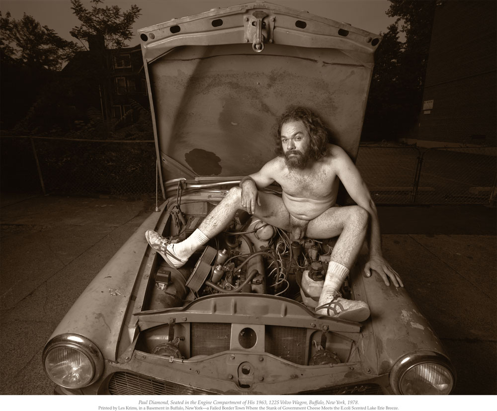 "Criminale - ©Les Krims, ""Paul Diamond seated in the engine compartment of his 1963, 122S Volvo Wagon,"" Buffalo, New York, 1978."