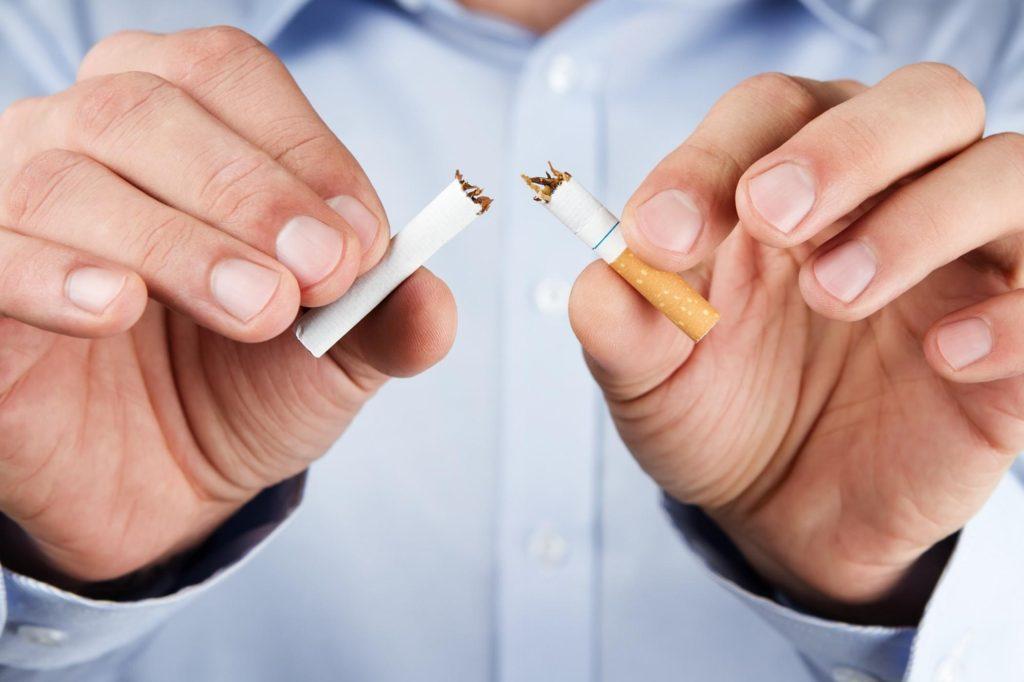Smettere di fumare - un uomo spezza in due una sigaretta