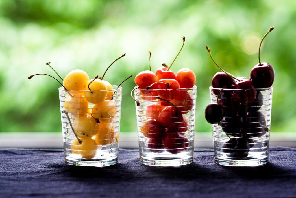Ciliegie gialle, arancioni e nere distribuite in tre bicchieri di vetro - Frutta per il diabete consigliata