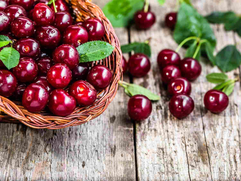 Ciliegie all'interno di un cestino in vimini e poggiate sul tavolo in legno - Frutta per il diabete consigliata