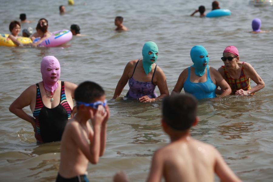 abbronzatura in Cina: donne con i facekini in una spiaggia di Qingdao