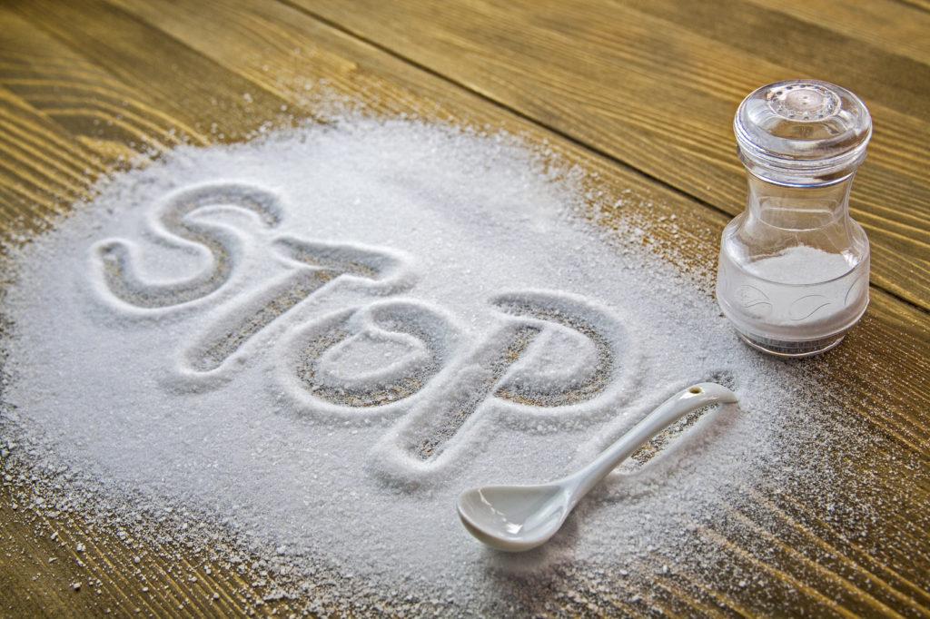 """Ridurre il sale da cucina - scritta """"stop"""" nel sale rovesciato sul tavolo"""