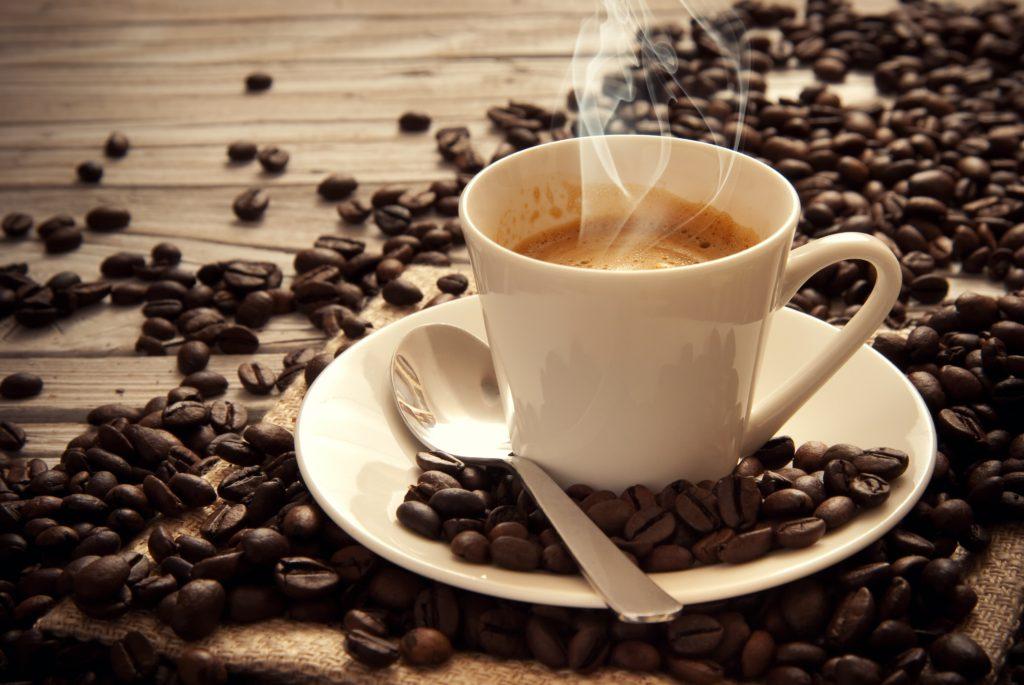 caffè espresso in tazzina bianca circondata dai chicchi tostati