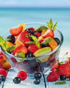 Cosa mangiare in estate - compertina - frutta di vari colori in una terrina di vetro e sparsa su un tavolo di legno in spiaggia