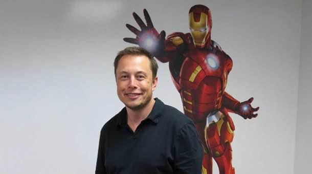 Elon Musk davanti a poster di Iron Man