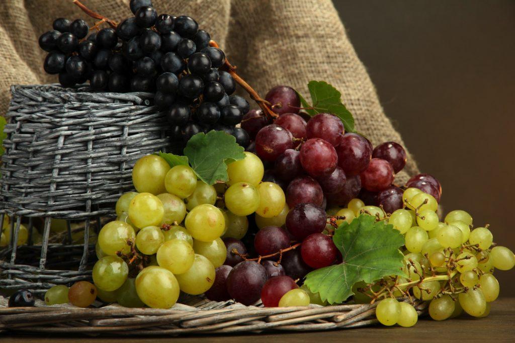 Varietà di uva: bianca, nera e rossa in un tavolo